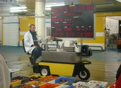 Un chef de vente et un mobyclock lors de la vente aux enchères
